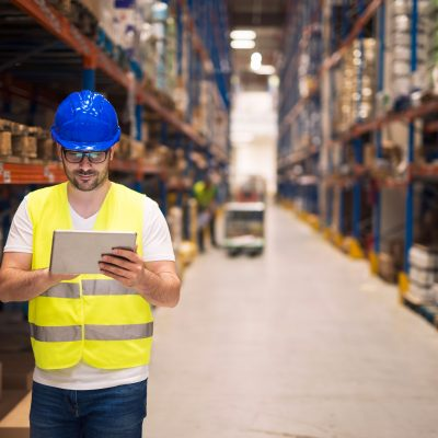 warehouse-worker-checking-inventory-on-his-tablet-while-walking-in-large-storage-department-with-shelves-and-packages-in-background